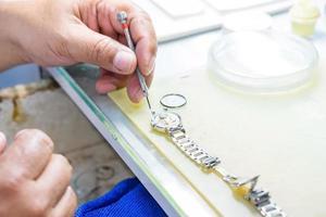 senior horlogemaker repareren van een oud horloge foto