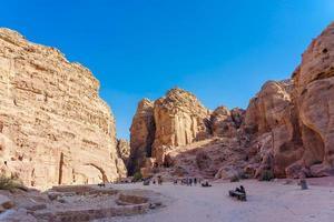 toeristen in de nauwe doorgang van rotsen van petra canyon in jordanië