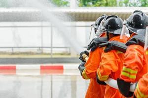 brandweerlieden die een brandblusser en water uit een slang gebruiken