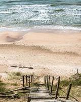 uitzicht op oude houten trappen naar de kust