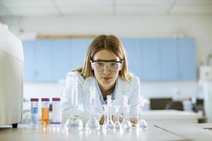 vrouwelijke medisch of wetenschappelijk onderzoeker kolven met oplossingen in een laboratorium kijken