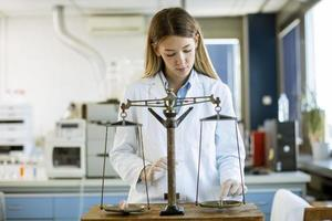 jonge vrouwelijke onderzoeker die het gewicht van het mineraalmonster in het laboratorium meet
