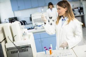 vrouwelijke arts die beschermend gezichtsmasker draagt in de kolf van de laboratoriumholding met vloeibaar monster foto