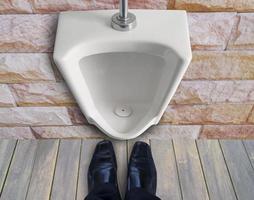 man die voor urinoir staat foto