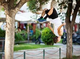 jonge sportman doet front flip in de straat foto
