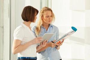 twee collega's praten terwijl ze naar een notitieboekje kijken foto
