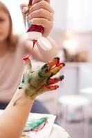 verf wordt aangebracht op de hand van een kind