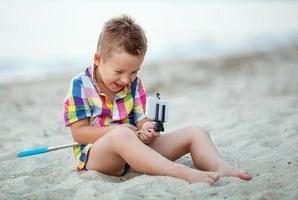 jongen met selfiestick op een strand