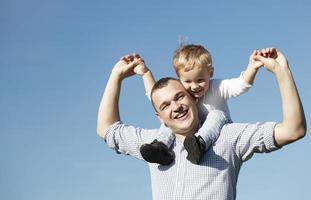 vader geeft zijn jonge zoon een ritje op de rug foto