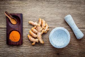 curcumine poeder en wortels met een vijzel foto