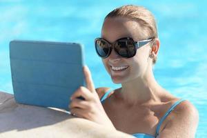 vrouw in een zwembad met behulp van een tablet