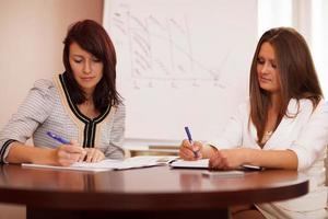twee vrouwen die aantekeningen maken tijdens een bedrijfspresentatie foto