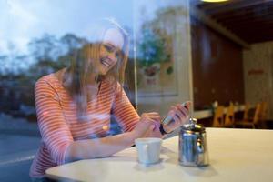 vrouw aan de telefoon in een café foto