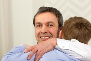 vader knuffelen zoon foto
