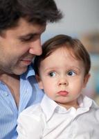 trieste jongen met vader foto