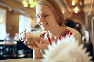 vrouw die een latte drinkt in een café foto