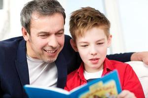 vader en zoon lezen van een boek foto
