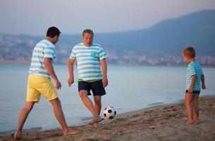 familie voetballen op een strand foto