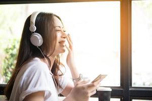 jonge vrouw luisteren naar muziek op koptelefoon met vensterbank achtergrond
