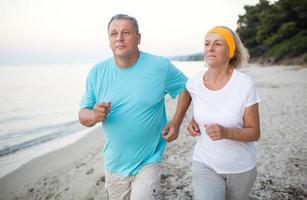 senior paar joggen op het strand foto