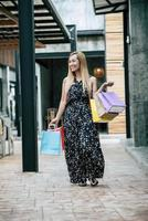 portret van een jonge vrouw gelukkig met boodschappentassen wandelen in de straat