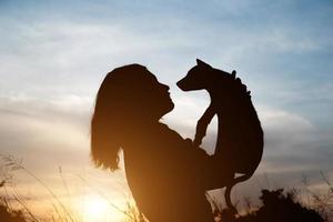 silhouet van vrouw met kleine hond bij zonsondergang veld