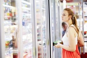 jonge vrouw bij de supermarkt foto