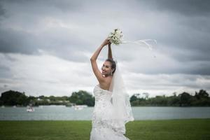 mooie bruid met bloemen, bruiloft make-up en kapsel foto