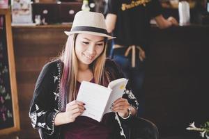 gelukkig zakenvrouw leesboek terwijl u ontspant in café
