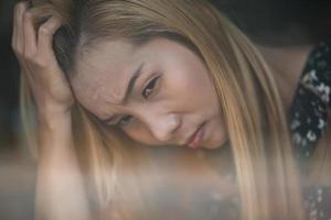 portret van een gestresste jonge vrouw, zittend in een café