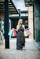 portret van een jonge vrouw gelukkig met boodschappentassen wandelen in de straat foto