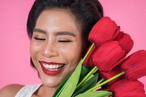 portret van een mooie vrouw met een boeket van rode tulp bloemen