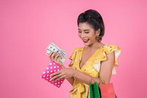jonge modieuze vrouw met een portemonnee met contant geld en boodschappentassen