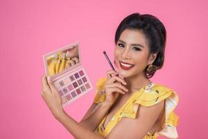 portret van een vrouw met make-up en cosmetische borstel