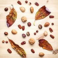 gedroogde bladeren en noten op een houten achtergrond foto
