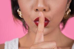 mooie Aziatische vrouw met rode lippen die stilte stilte teken tonen foto