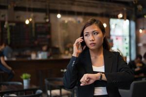 mooie zakenvrouw praten op mobiele telefoon kijken hand horloge over cafe achtergrond