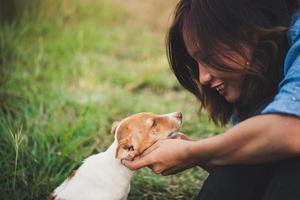 gelukkig vrolijk hipster meisje speelt met haar hond in het park tijdens zonsondergang