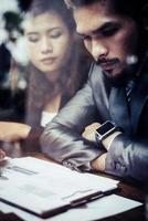 zakenvrienden analyseren documenten terwijl ze een pauze nemen in een café