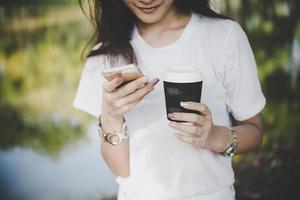 jonge vrouw met wegwerp koffiekopje terwijl tekstberichten via smartphone buitenshuis