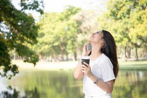 jonge mooie vrouw met wegwerp koffiekopje tijdens het gesprek aan de telefoon