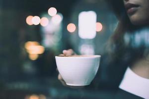 jonge vrouw ontspannen koffie drinken in café foto