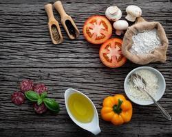 verse pizza-ingrediënten op donker hout foto