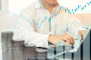 persoon die aan een bureau werkt met een grafiek en munten overlay foto