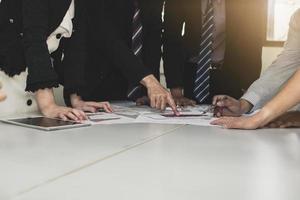 team van mensen uit het bedrijfsleven plannen aan een vergadertafel foto