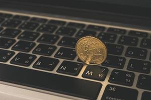 gouden munt op laptop toetsenbord foto