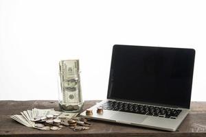 laptop met munten en dollarbank geïsoleerd op een witte achtergrond foto