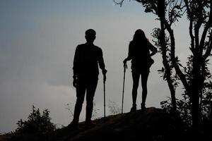 silhouet van paar wandelaars op de top van een berg