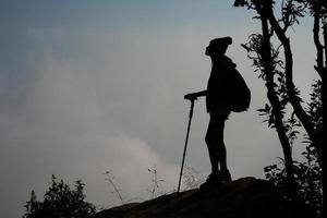 silhouet van wandelaar op de top van een berg