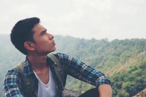jonge hipster wandelaar met rugzak zittend op de top van de berg foto
